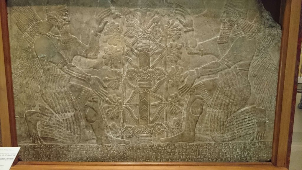 Ancient persian wall carvings depicting to men tending to the tree of life